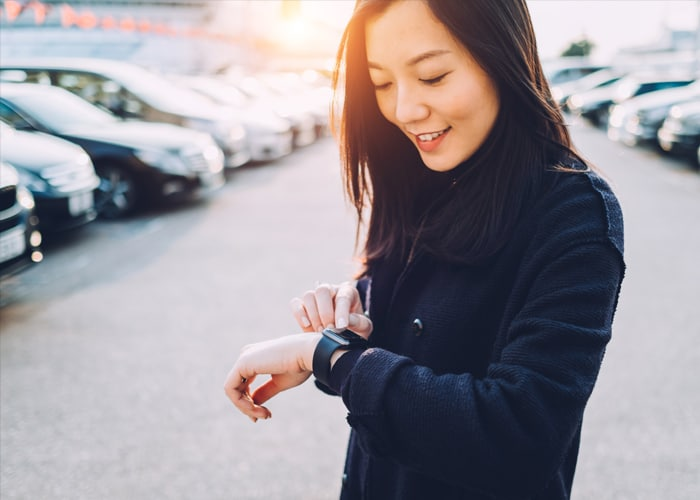A woman smiling and looking at her watch.