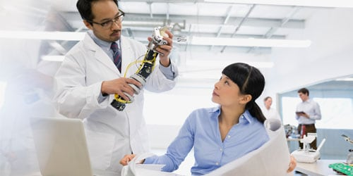 man showing robotic arm to woman