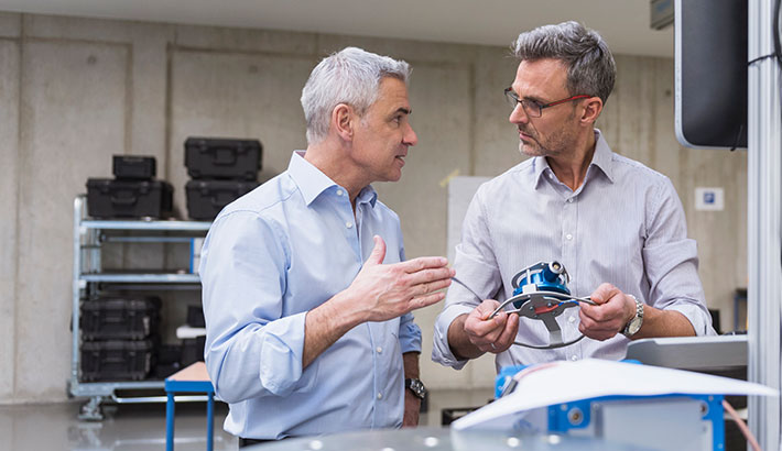 Professionals discussing over a product in hand