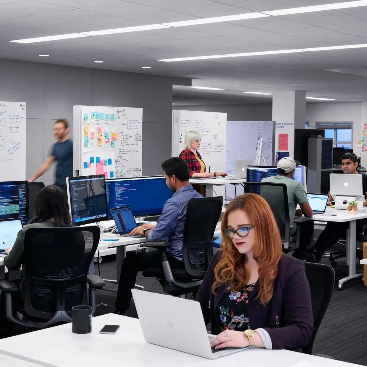 Several employees at and around desks with computers