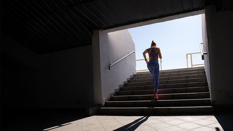 Young woman running up stadium steps