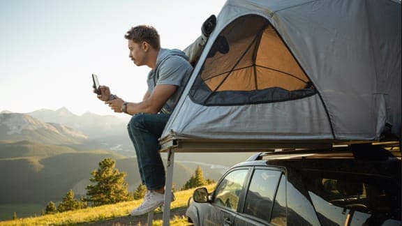 Person looking at cellphone while sitting at a camping tent