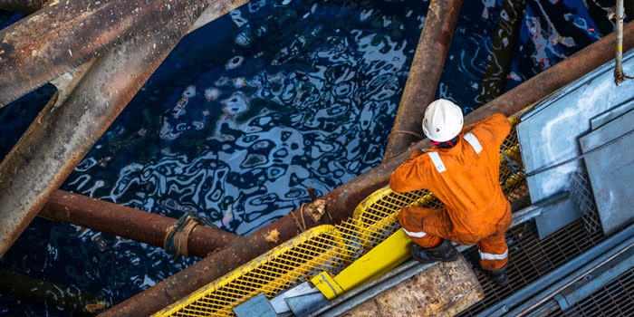 Oil worker looking over the side of a rig