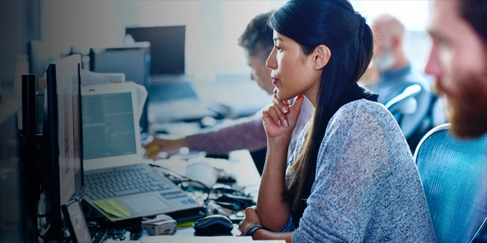 Woman with her hand in her chin looking at her monitor