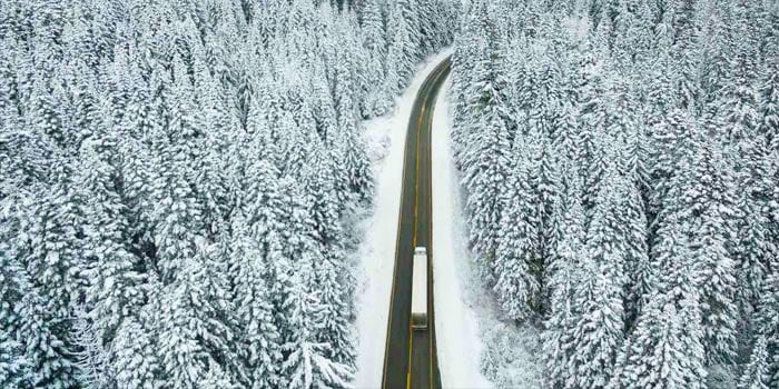 Aerial view of a road through a snowy forest with one large truck on it