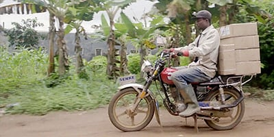 Man transporting packages on a motorcycle in a tropical setting