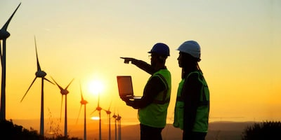 Two men dressed in safety gear standing and pointing at a wind farm at sunset