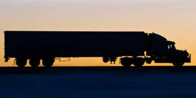 Side view of a large cargo truck at sunset