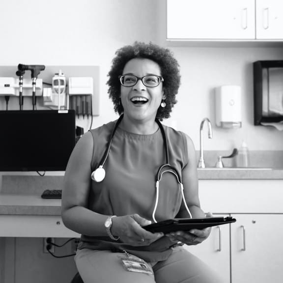 A doctor sitting and laughing with a tablet in her hands