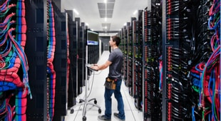 Man standing in aisle of large data center with rows of storage arrays