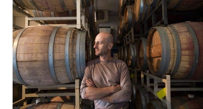 Man standing with wine barrels