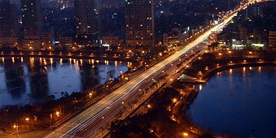 Overhead view of a city at night featuring a bridge over a river