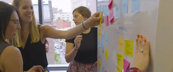 Image of people looking at a post-its board while a woman is picking one post-it