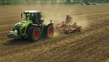 a tractor being used on cropping a field