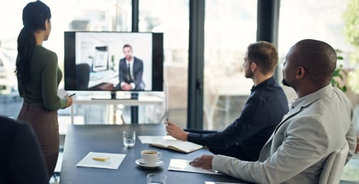 Three people on a conference room watching a person talk on a video call