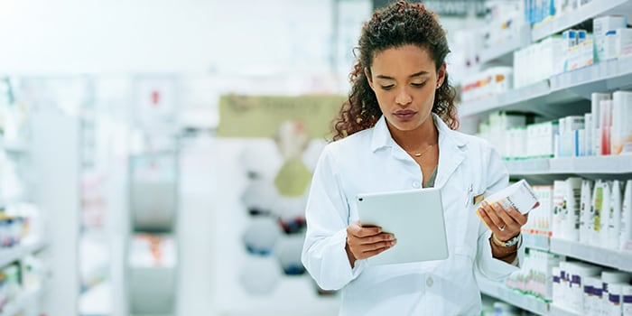a pharmaceutical woman looking at some medicines and checking her tablet