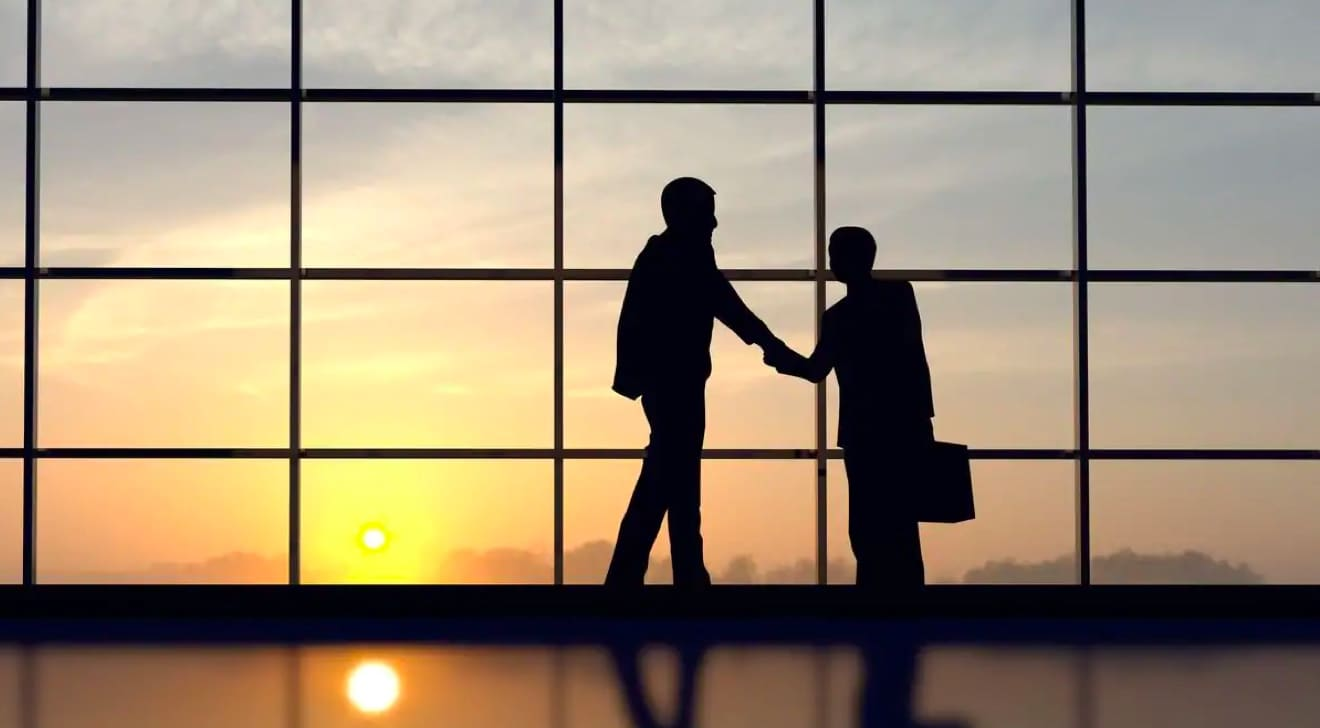 Two business men shaking hands in front of window