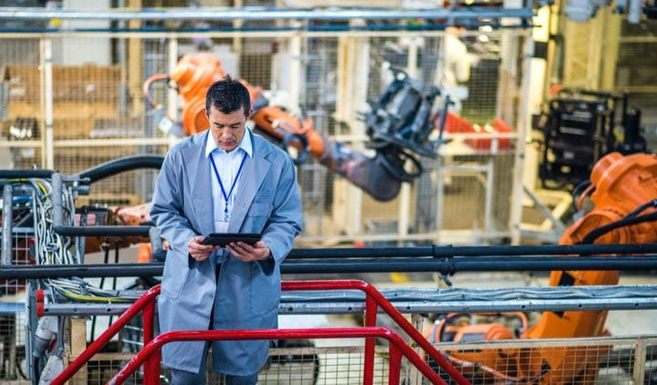 man in assembly factory looking at his electronic tablet
