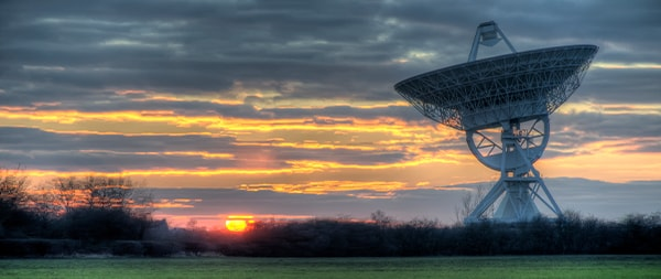 a ground satellite station in contrast with a sunset