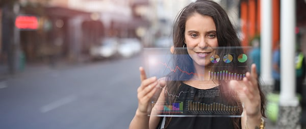 futuristic representation of a woman holding a glass with some charts being displayed on it