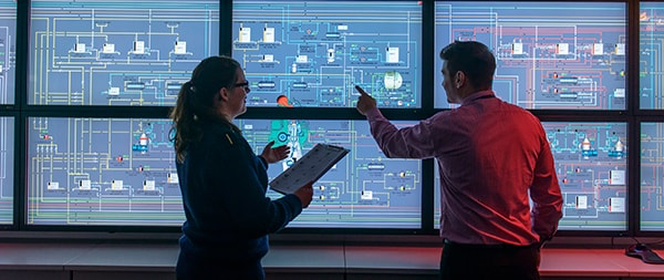 two people looking at a wall of monitors displaying the map of several servers