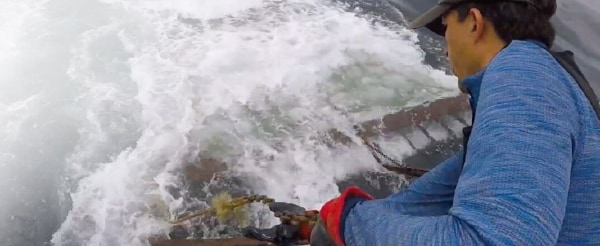 Fisherman pulling a chain from the ocean