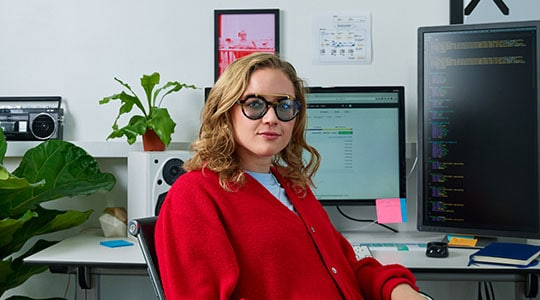 Woman with glasses sitting in front of desk with multiple monitors