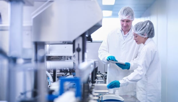 Two employees dressed in protective clothing in a pharmaceutical manufacturing facility