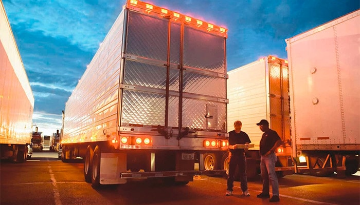 Two men talking next to semi trucks in a large parking lot