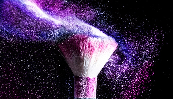Close up of a makeup brush with powdered makeup flying off the brush