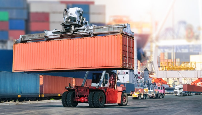 a machine carrying a container at a seaport