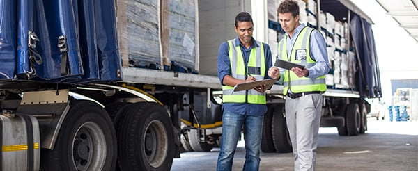 Two workers stand beside trucks and compare shipping documents