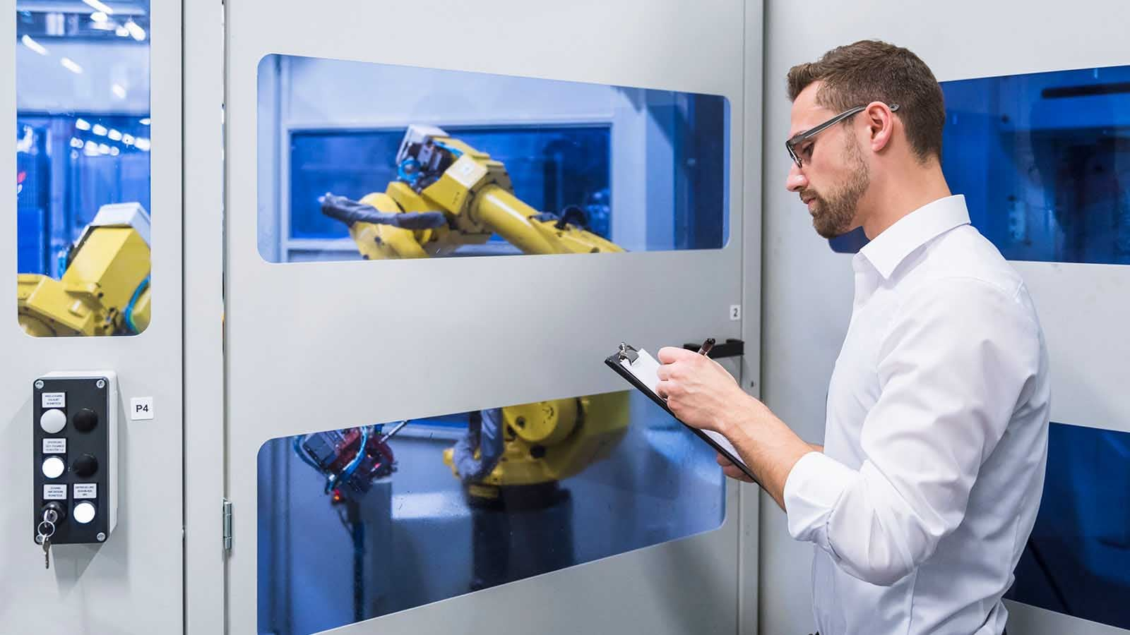 Man checking industrial robotic device