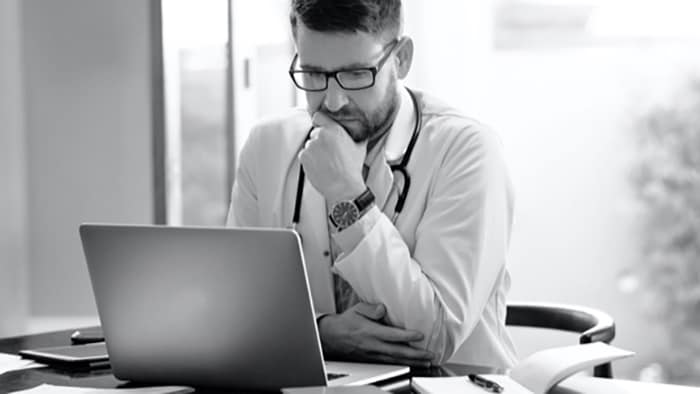 Healthcare provider looking at laptop computer while thinking