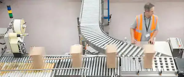 Worker managing the conveyor belt in a packaging facility