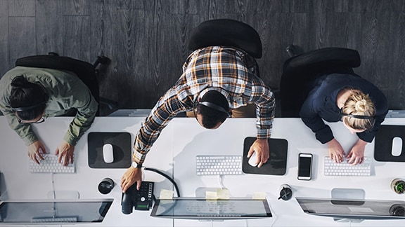 Top view of three people working in an office
