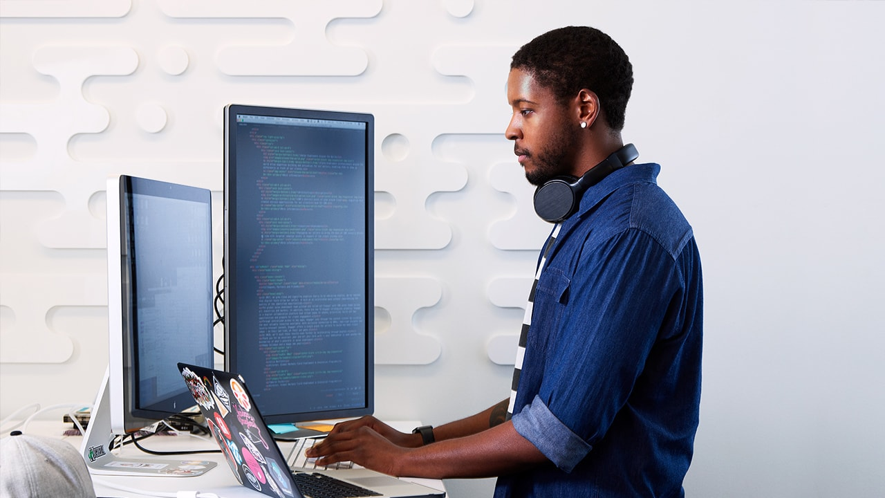 man working with multiple monitors