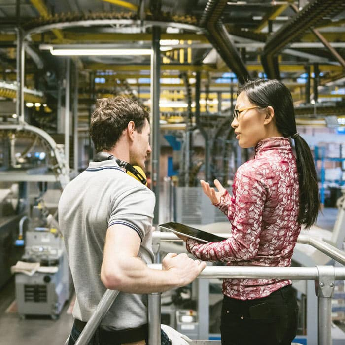 Woman holding tablet in discussion with man in industrial setting