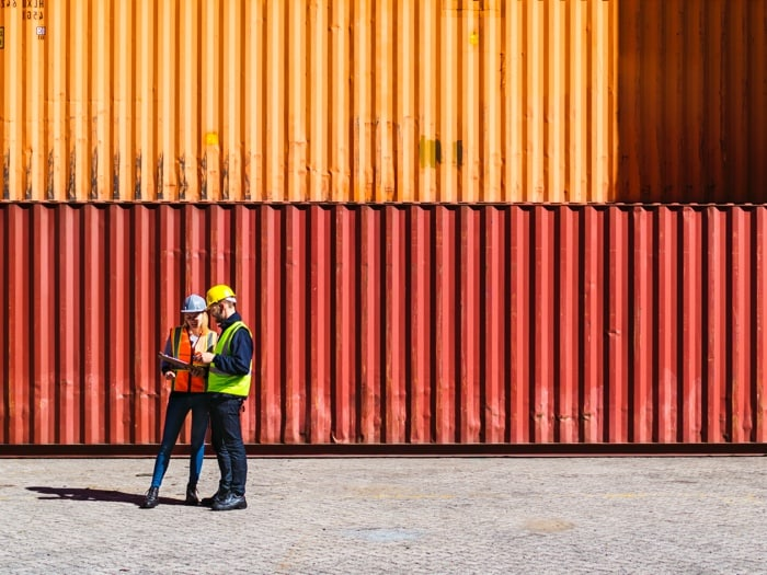 Man and woman wearing hard hats looking at a tablet while standing in front of orange shipping containers