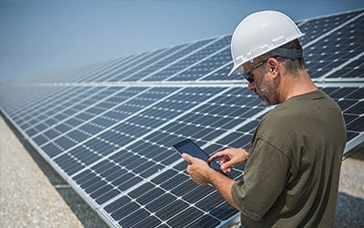 engineer with helmet using a smartphone with solar panels on the background