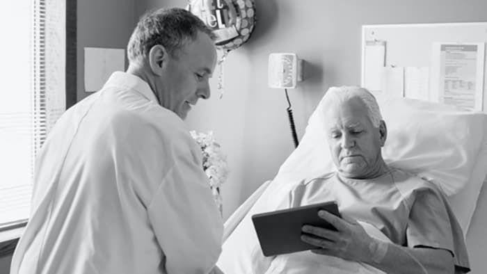 Patient looking at tablet in hospital bed