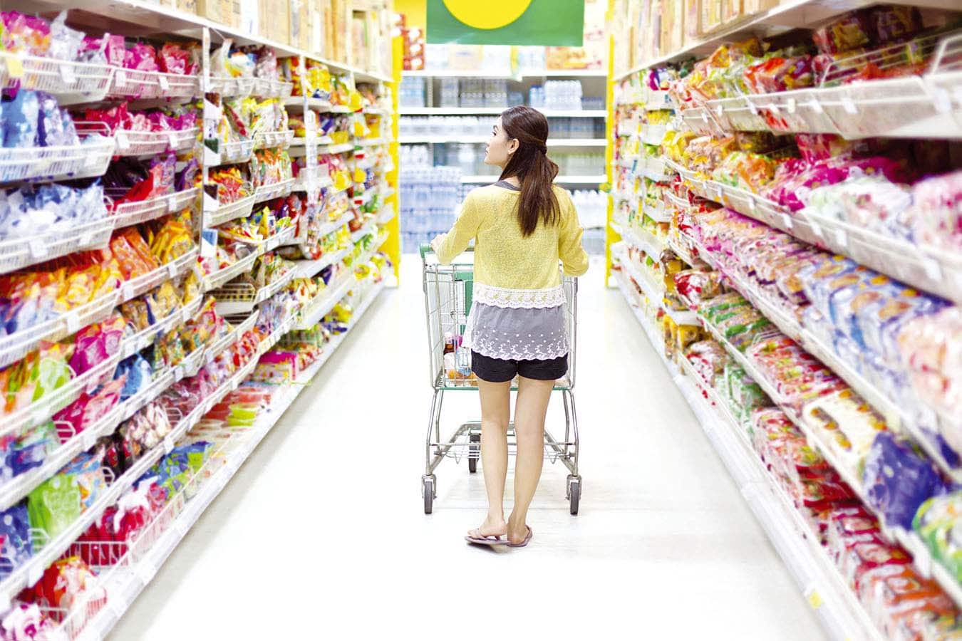 Shopper with grocery cart walking down store aisle