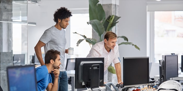 Three guys looking at a computer monitor