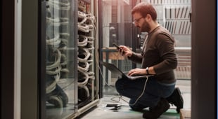 man kneeling on the floor next to a server cabinet