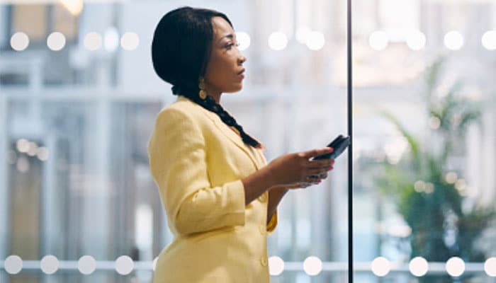 A business woman uses her mobile device before a meeting