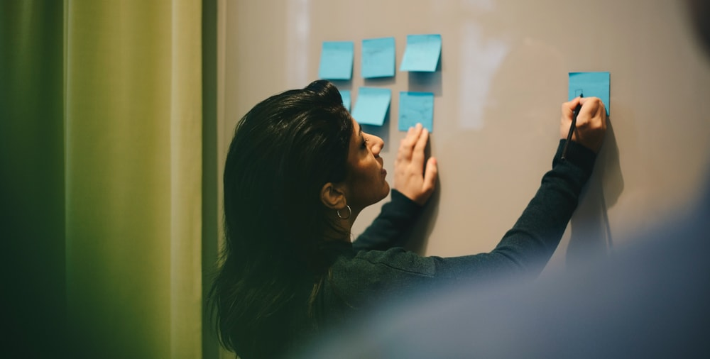 a woman placing some post its in a wall