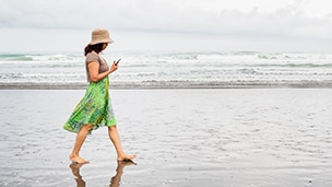 a woman refers to her cell phone as she walks on a beach