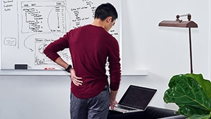 a man stands near a whiteboard looking at laptop computer