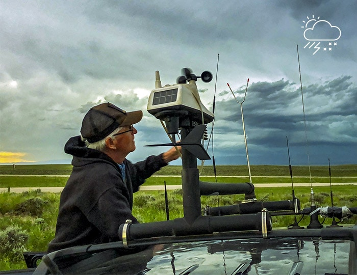 Man adjusting a weather tracking device on the top of a vehicle