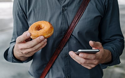 man holding a donut and a cell phone